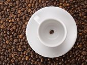 A white cup with one coffee bean on beans background
