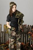 A beautiful young teen by a rustic old fence.  She's wearing camo pants, hat, and gloves and carries her jacket over her shoulder.  On a gray background.