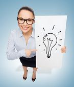 business and advertisement concept - smiling businesswoman in eyeglasses pointing finger to white board with light bulb