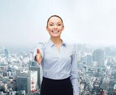 business, gesture and education concept - friendly young smiling businesswoman with opened hand read