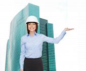 building, developing, advertising and architecture concept - friendly young smiling businesswoman in