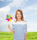 education, childhood and ecology concept - smiling child with colorful windmill toy