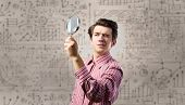 Young man scientist looking in magnifying glass