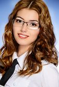 Close-up portrait of a beautiful young woman in white blouse, tie and spectacles.