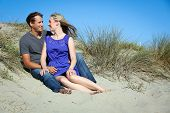 Young attractive couple sitting in sand