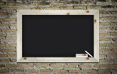 Empty Blackboard With Wooden Frame And Chalks On Wall Background