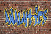 analytics word -  graffiti style text on a old grunge brick wall