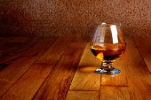 One Glass Of Brandy On Antique Wooden Counter Top