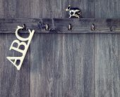 ABC letters hanging on nursery wall with toy cow