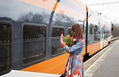 Woman With Flowers Salute To Train Passanger