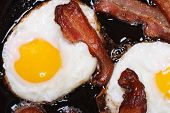 Fried Eggs With Bacon In A Pan Top View