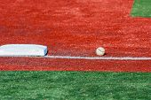 stock photo of infield  - A base and a ball on an infield of a baseball field - JPG
