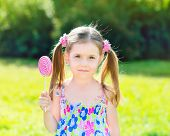 Adorable Little Girl With Two Blond Ponytails Holding White And Pink Lollipop In Her Hand, Outdoor S