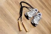 foto of jump rope  - Jumping rope and trainers on a gym floor - JPG
