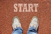 A Pair Of Feet On A Running Track Rubber With White Print Of The Word Start, Concept Of Starting Poi
