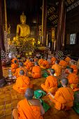 CHIANG MAI, THAILAND - NOVEMBER 22, 2013: Young buddhist monks praying in front of the Buddha image