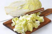 chopped chinese cabbage and kitchen knife on wooden cutting board