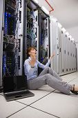 Stressed technician sitting on floor beside open server in large data center