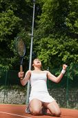 Pretty tennis player celebrating a win on a sunny day