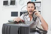 Angry computer engineer making a call in his office
