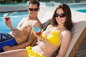 Portrait of a smiling young couple with drinks sitting by swimming pool