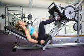 Side view of a fit young woman doing leg presses in the gym