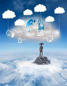 Businessman standing under umbrella against mountain peak through the clouds