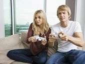 Relaxed young couple playing video game in living room at home
