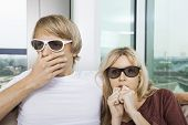 Couple wearing 3D glasses and watching TV with concentration at home