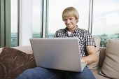 Smiling mid-adult man using laptop on sofa at home