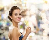 party, drinks, holidays, luxury and celebration concept - smiling woman in evening dress with glass
