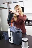 Portrait of woman using juicer for juicing carrots at kitchen counter