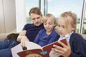 Father and children reading storybook on sofa at home