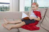 Happy little boy in superhero costume reading book on sofa at home