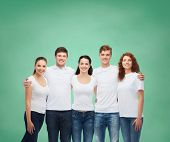 advertising, friendship, education, school and people concept - group of smiling teenagers in white blank t-shirts standing over green board background