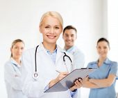 healthcare and medicine concept - smiling female doctor with stethoscope and clipboard