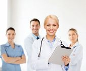 healthcare, technology and medicine concept - smiling female doctor with stethoscope and tablet pc c