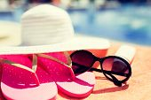 beach, summer and vacation concept - close up of hat, flip-flops, sunscreen and sunglasses at pool