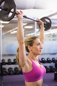 Side view of a fit young woman lifting barbell in the gym