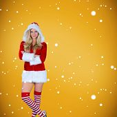 Pretty girl in santa outfit with arms crossed against yellow background with vignette
