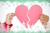 Couple holding two halves of broken heart against green snowflake design