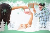 Happy young couple putting up picture frame against snowflakes and fir tree in green