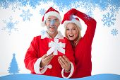Festive couple smiling and holding gift against snow flake frame in blue