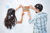 Happy young couple putting up picture frame against snow falling