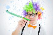 Geeky hipster wearing a rainbow wig blowing party horn against snow falling