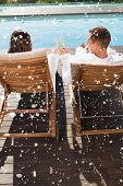 Couple toasting champagne by swimming pool against snow falling