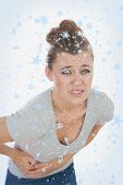 Young woman suffering from stomach pain against snow falling