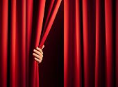 stock photo of curtains stage  - male hand in the act of disclose the scene shifting the red curtain - JPG