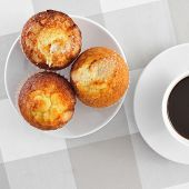 a plate with some magdalenas, typical spanish plain muffins, and a cup of coffee on a set table