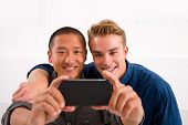 Two Smiling Young Men Taking Self Portrait With Cell Phone